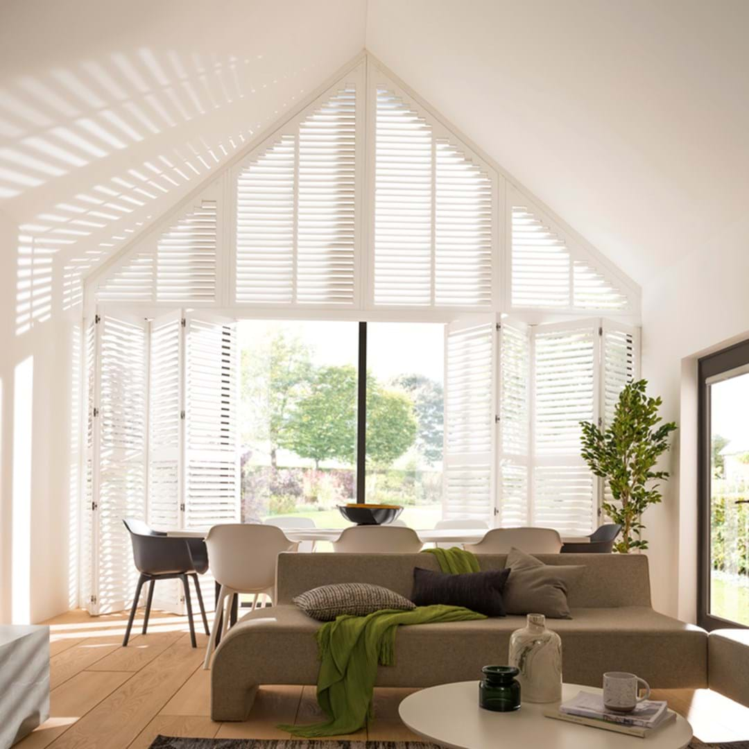 White coloured shutters that are fitted to a gable shaped window in a living room