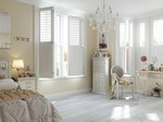 White shutters fitted to a large rectangular window in a bedroom that is decorated in cream