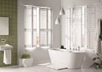 White folding shutters in a bathroom that is decorated in white and has green wall tiles