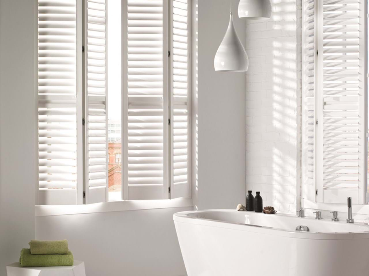 White coloured folding shutters in a white decorated bathroom