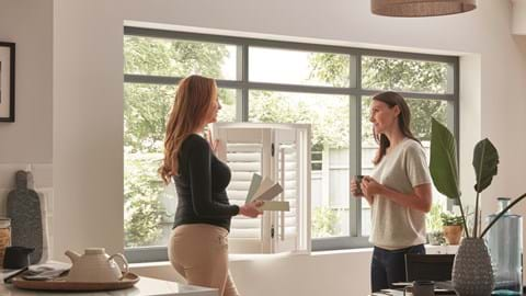 A Thomas Sanderson advisor showing a white shutter to a customer in there home while also holding a variety of swatches