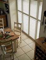 Tier on tier shutters on a tall rectangular shaped window in a dining room that is decorated with white and wooden tones