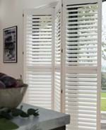 White tracked shutters that have been adjusted to show how easily they fold  and are fitted to a large rectangular door window