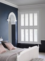 Tier on tier shutters which are coloured white are fitted to a rectangular shaped window in a bedroom that is decorated with navy blue walls