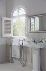 Shutters in a white colour that are fitted to an arch shaped window in a bathroom that is decorated in white and has steel features