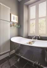 Tier on tier shutters which are white in colour have been fitted to a rectnagular shaped window in a bathroom that is decorated with grey tones