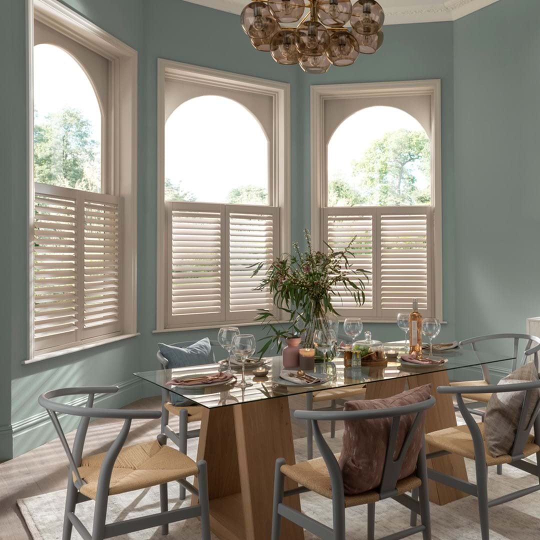 Cafe styled shutters in white fitted to arch shaped windows in a dining room that is decorated with light green walls