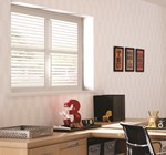 Full height shutters are fitted to a square window in an office setting