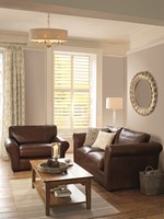 full height shutters on rectangular windows in a room that is decorated with white walls, a brown sofa, armchair and coffee table