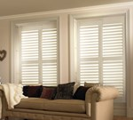 Two white full height shutters fitted to a rectangular shaped window in a living room featuring a sofa
