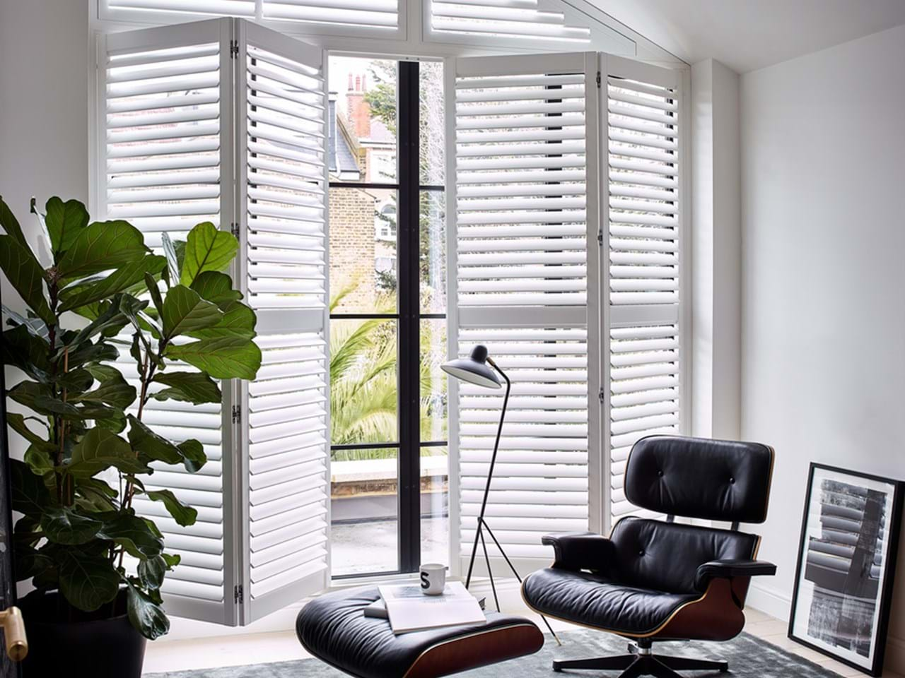 White tracked shutters fitted to a rectangular window to a slanted shaped window in a living room featuring a black armchair, footrest and plant