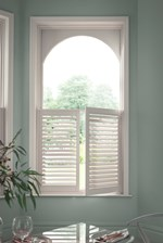 White cafe style shutters fitted to an arch shaped window in a dining room