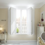 White solid shutters fitted to a rectangular window in a room that is decorated with cream walls