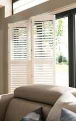 White tracked shutters on a door window which has been folded slightly to let in daylight to a living room