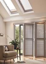 A grey coloured tracked shutter which is on a sliding window door in a living room decorated in white