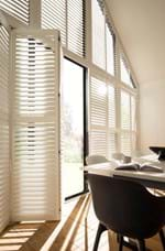 White tracked shutters that are on a gable end shape window in a dining room decorated in white