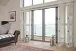 White tracked shutters fitted to large door windows in a living room decorated with white walls