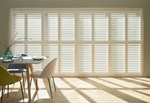 A series of white tracked shutters fitted to a wide rectangular window in a dining room decorated in light colours