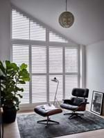White tracked shutters fitted to a slanted window in a room that features a black armchair, footrest and plant