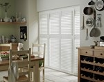 White tracked shutters fitted to a rectangular shaped window in a kitchen setting that is decorated in white