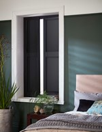 Black coloured solid shutters which are fitted to a rectangular shaped window in a bedroom decorated with green walls