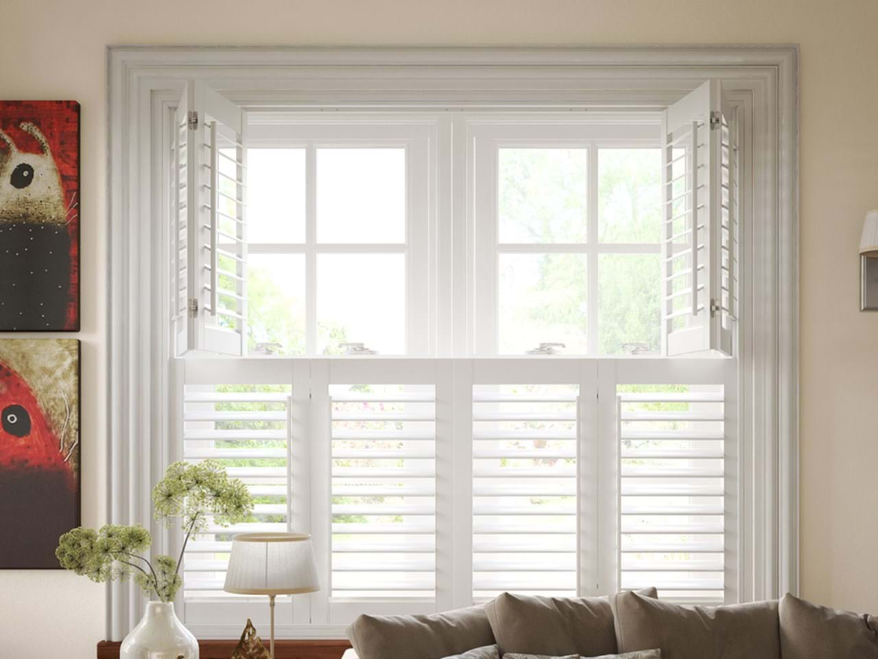 White tier on tier shutters that have been fitted to a rectangular shaped window in a living room with cream walls