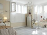 white tier on tier shutters fitted to multiple windows in a bedroom decorated in cream and white