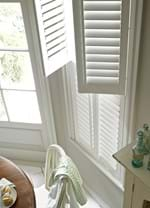 White coloured tier on tier shutters fitted to windows in a dining room