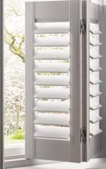 A white coloured tier on tier shutter folded slightly to let in natural daylight