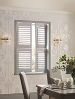 White tier on tier shutters in a dining room that is decorated with intricately styled wallpaper