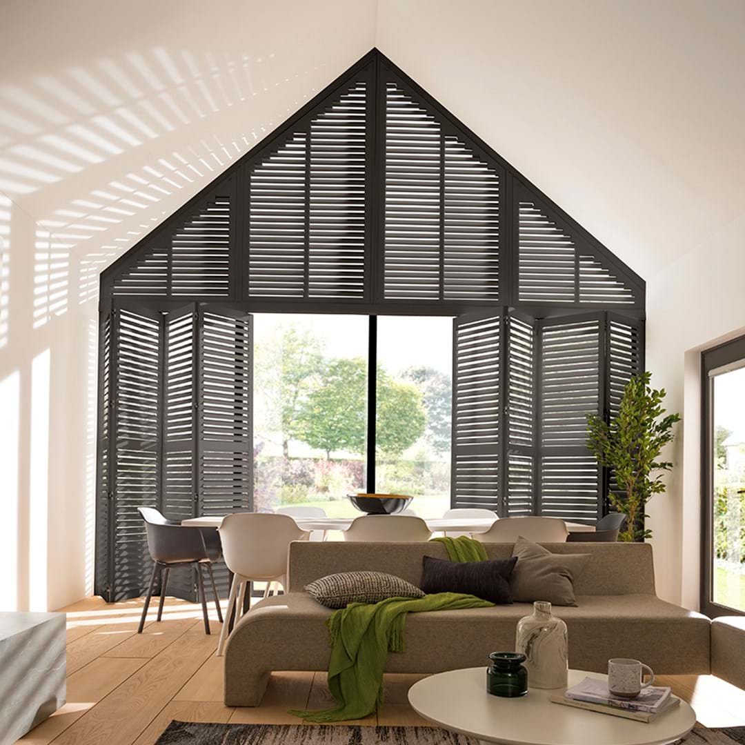 black coloured shutters fitted to a gable end window in a lving room setting of a light decorated room