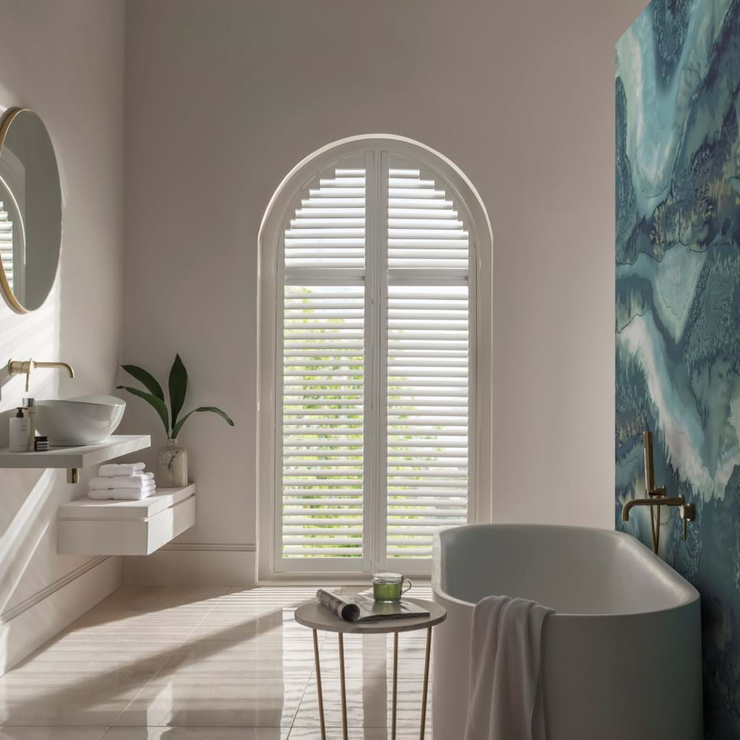 White arch shaped shutters fitted to an arch shaped window in a bathroom