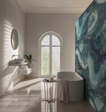 Shutters that are white in colour and are fitted to an arch shaped window in a bathroom that is also decorated in white