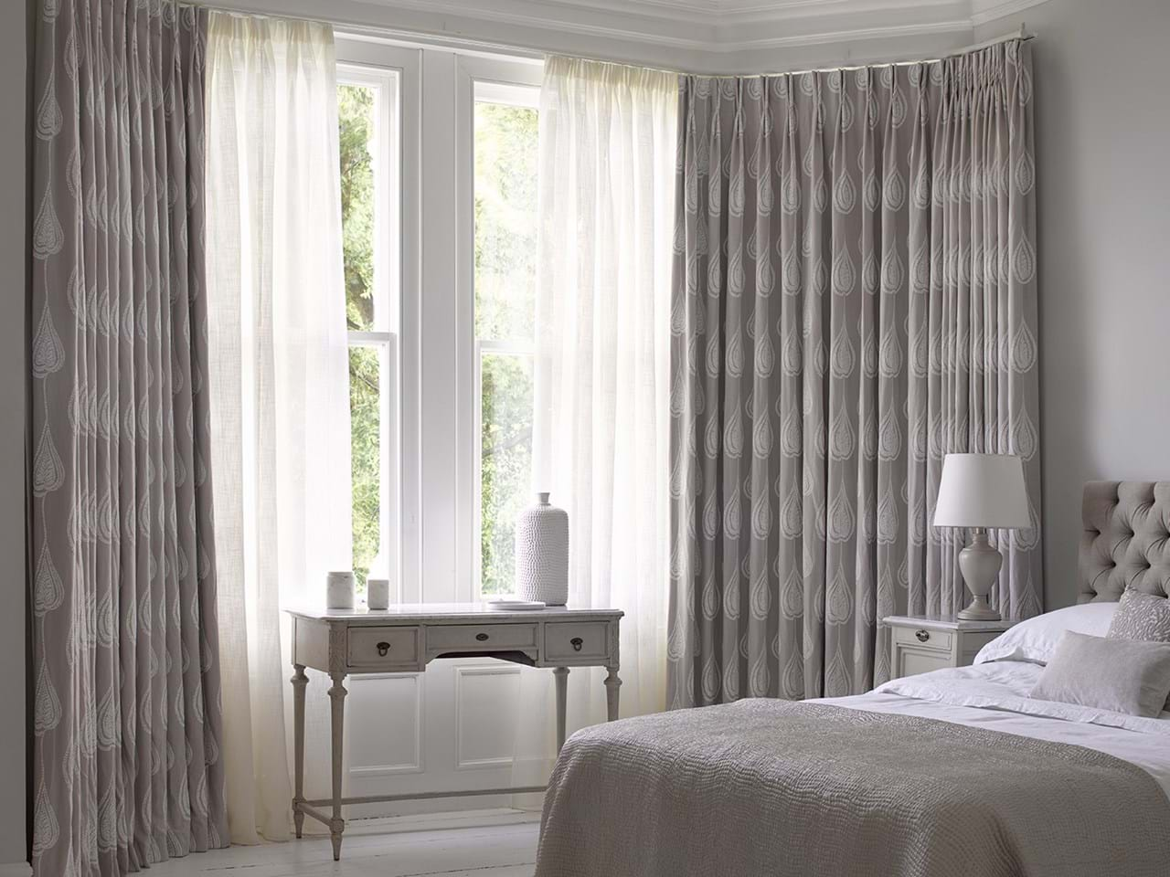 grey curtains matched with voile curtains on a door window in a bedroom decorated in grey and features a bed side table