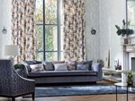 Florally decorated harlequin curtains with a white base colour have been fitted to a tall window in a living room that has white coloured walls with a silver pattern along with a blue sofa, chair and rug