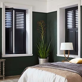 Black window shutters in bedroom