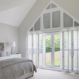 Shaped plantation shutters in bedroom