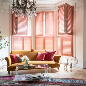 Pink tier-on-tier wooden shutters in living room