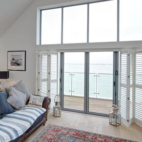 White shutters covering large patio doors in living room