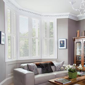White full height shutters covering bay window in living room