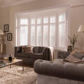 White plantation shutters in a living room bay window