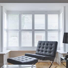 White shutters in a modern bay window