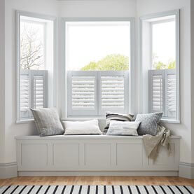 White café shutters next to a window seat in a living room