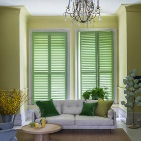 Green full height plantation shutters in living room