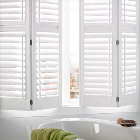 Waterproof white shutters next to a bath