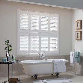 White tier-on-tier shutters next to a bath