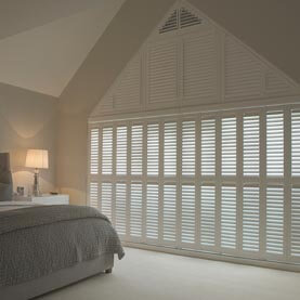 Shaped bedroom shutters on gable wall