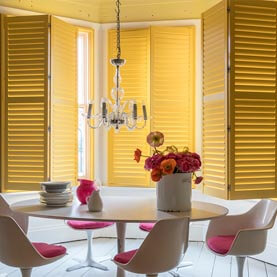 Yellow full height shutters in dining room
