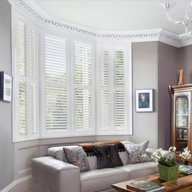 Bay window plantation shutters in a living room
