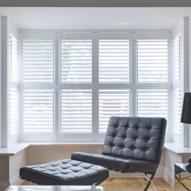 White shutters in a modern, square-like bay window